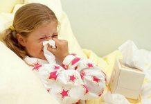 Devojčica u krevetu briše nos