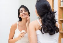 Devojka maže kremu za lice pred ogledalom