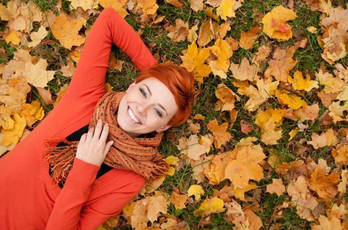 Devojka leži po opalom jesenjem lišću